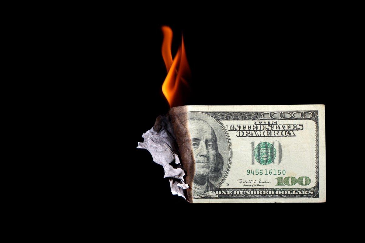 100 dollar bill burning -- wasting money cash