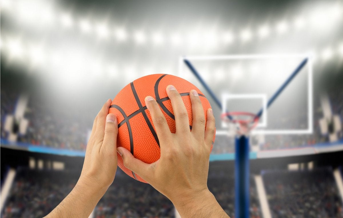 Man holding basketball in hands aiming for hoop.