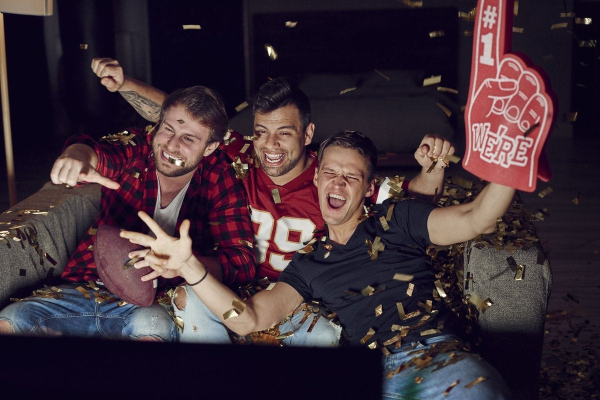 Men watching football on a television.