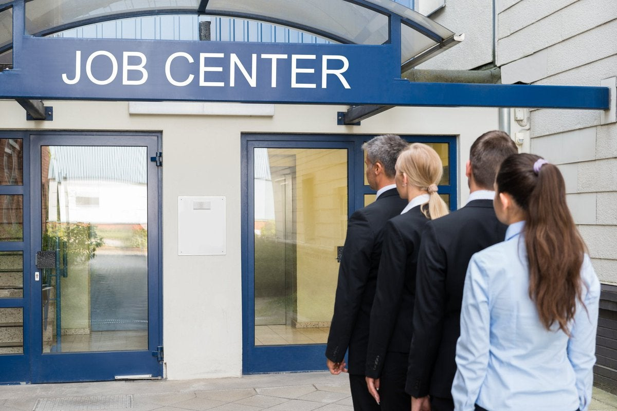A line of people standing in front of a building labeled Job Center.