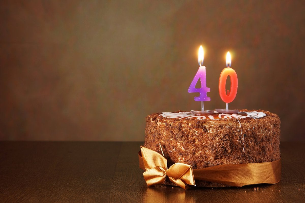 A chocolate birthday cake with candles that say 40.