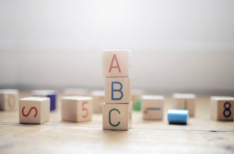 Wooden blocks scattered on the floor with ABC in the foreground.