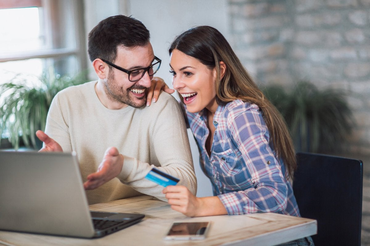 Young couple appear to be pleased about something they're viewing on a laptop while woman holds a credit card.