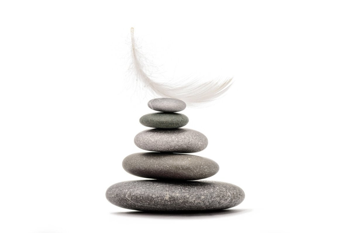 a feather resting on top of a pile of stones