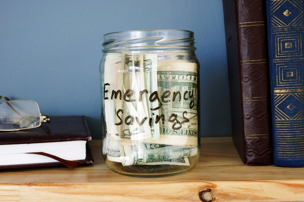 A jar that says emergency savings is on a bookshelf and full of cash.