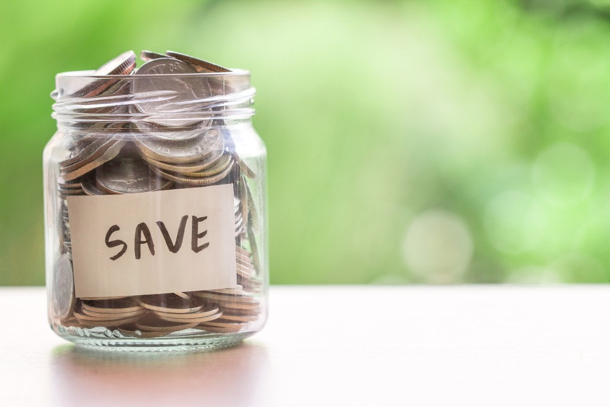 A jar full of coins with Save written on the side.