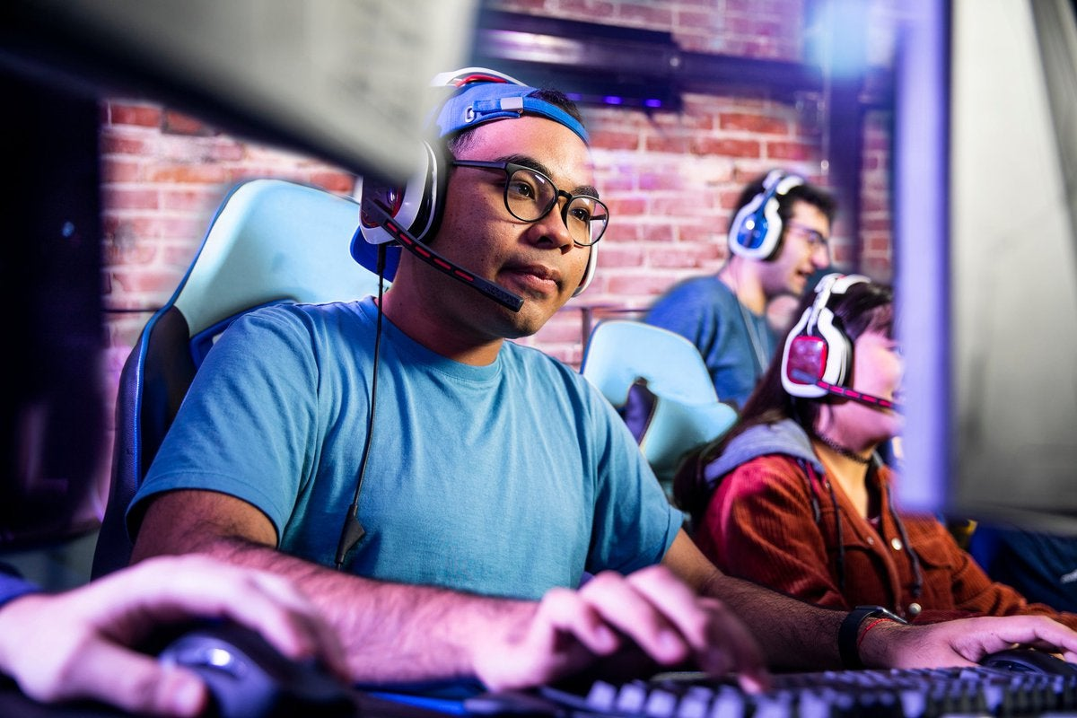 Adults engaging in computer gaming in a room together.