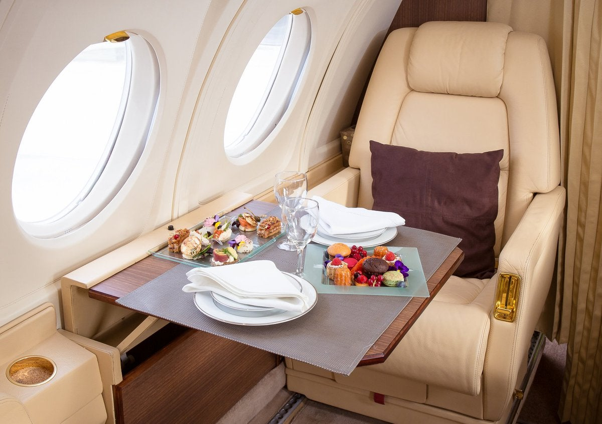 A first class seat in an airplane with fancy foods on the table.