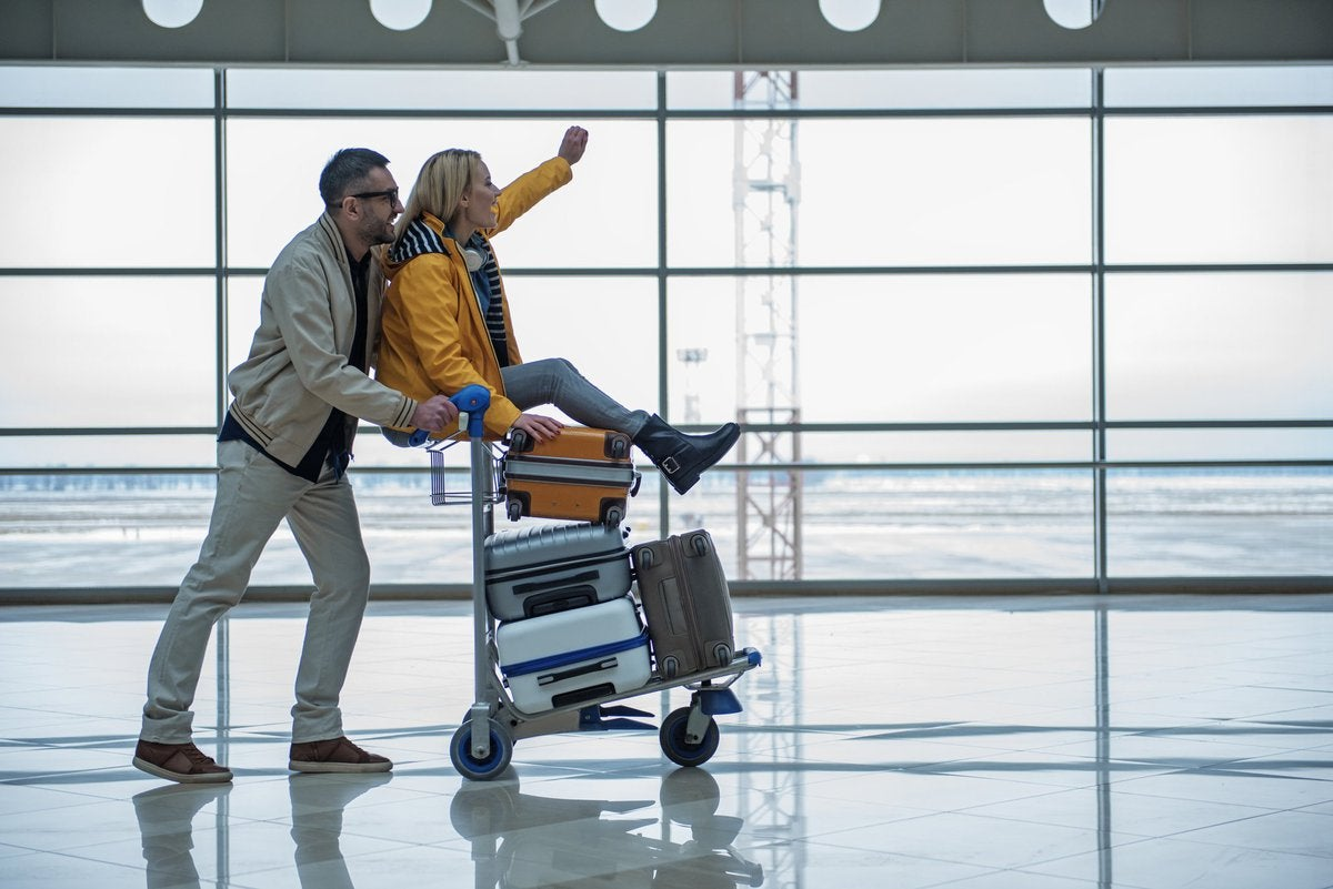A man pushing a luggage cart through an airport with a cheering woman on top.