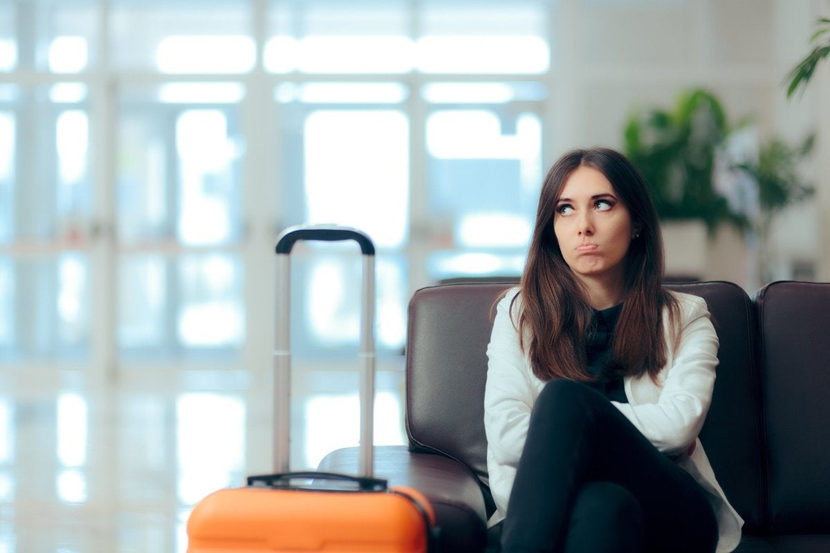 A frowning woman sitting next to her suitcase in an airport with her arms crossed.