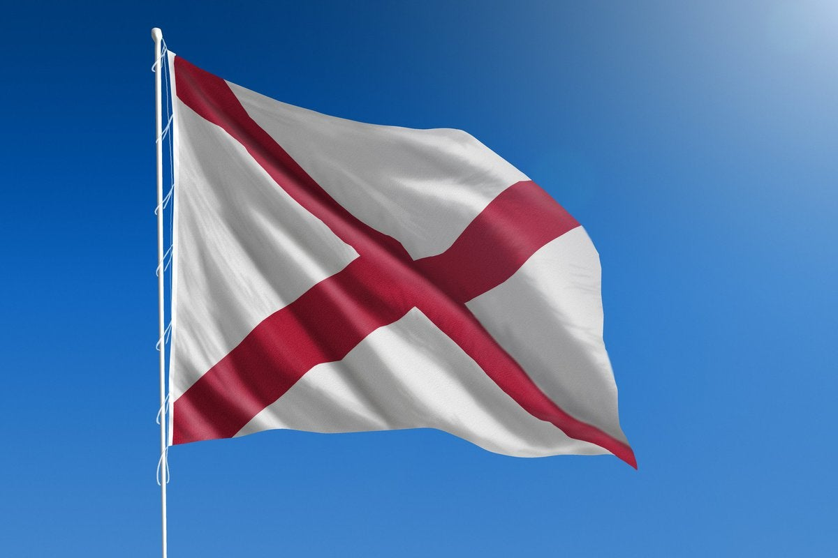 The Alabama state flag in front of a blue sky.