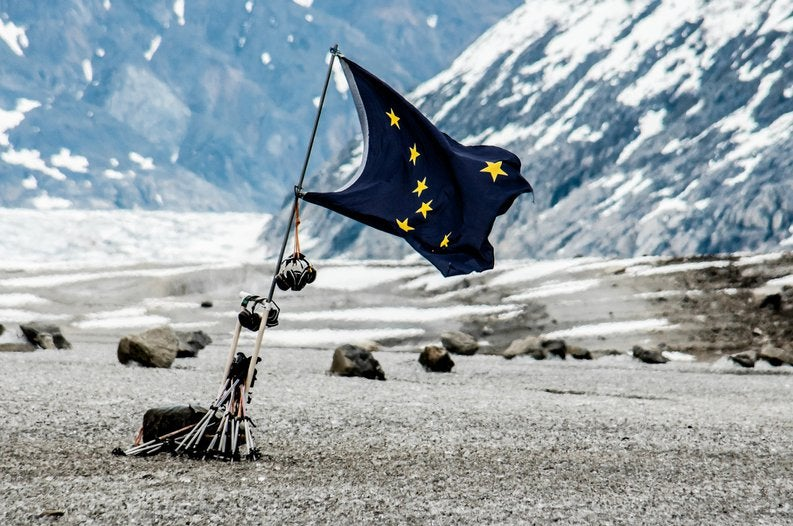 The state flag of Alaska fluttering in front of a mountainous open space..