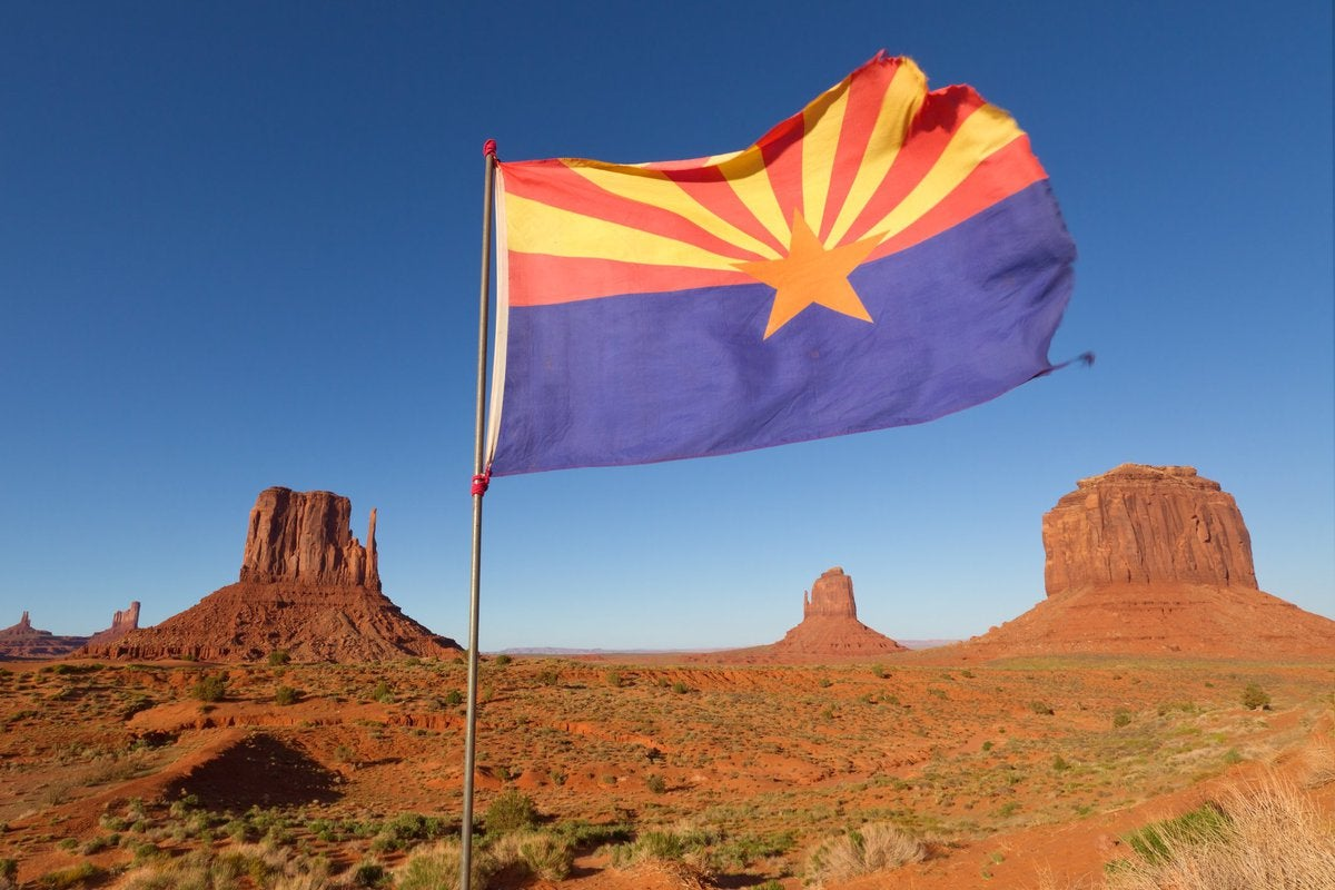 The Arizona state flag flying in front of rock formations in the desert.