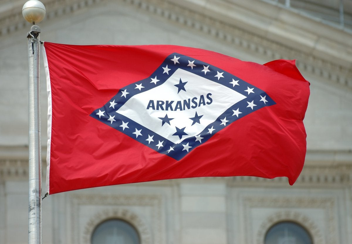 The Arkansas state flag flying in front of a courthouse.