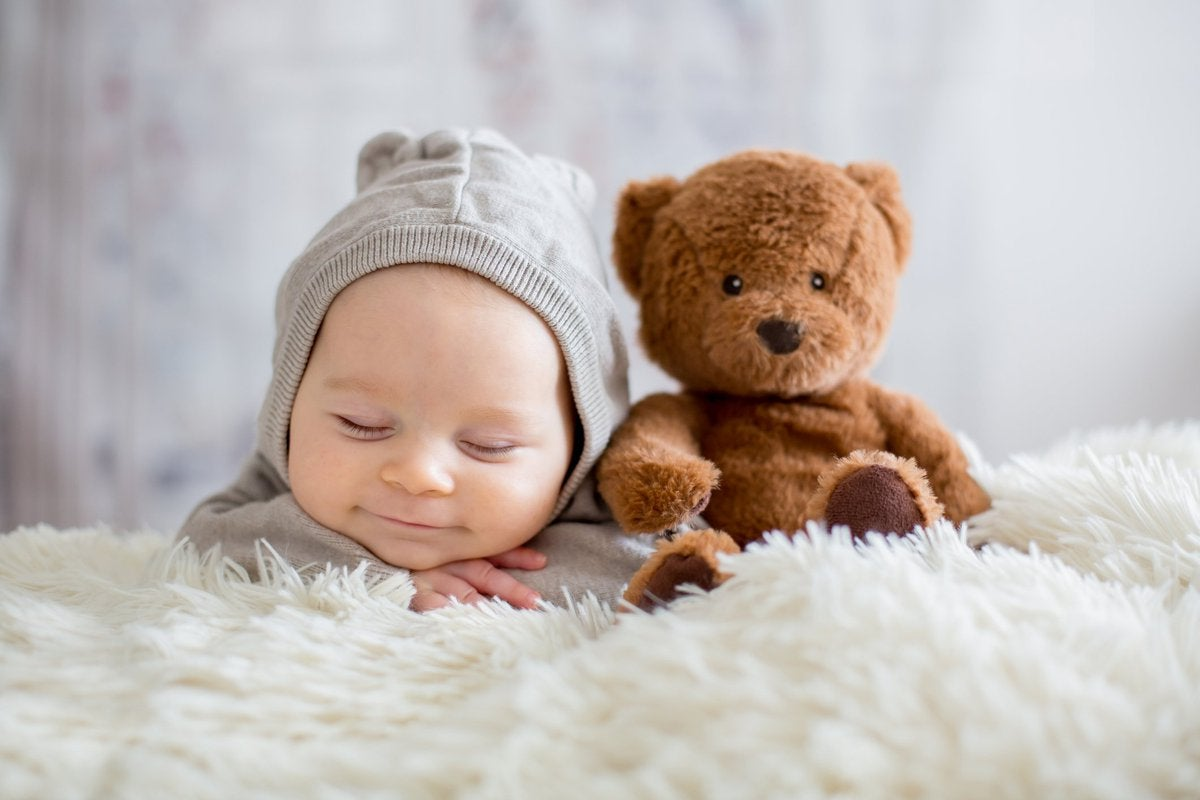Sleepy, smiling baby in a knit hat next to a teddy bear on a fuzzy blanket.