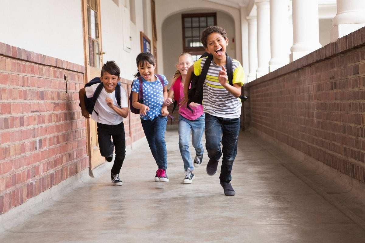 Cute pupils running down the hall in school.