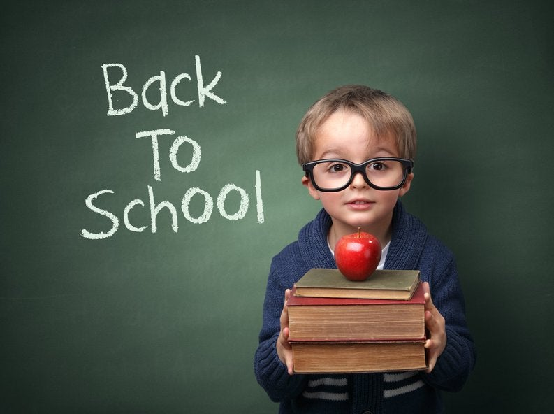 A child holding books and an apple in front of a chalk board that says Back To School.