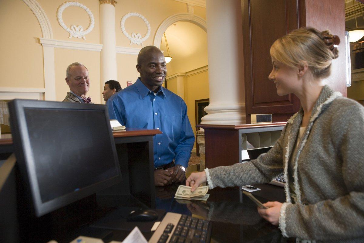 Man at bank smiling as teller hands him cash.
