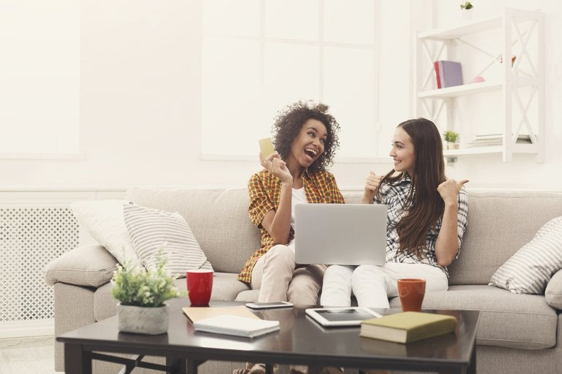 Two Excited Women Sitting On Sofa Using Laptop As One Of Them Holds Her Credit Card