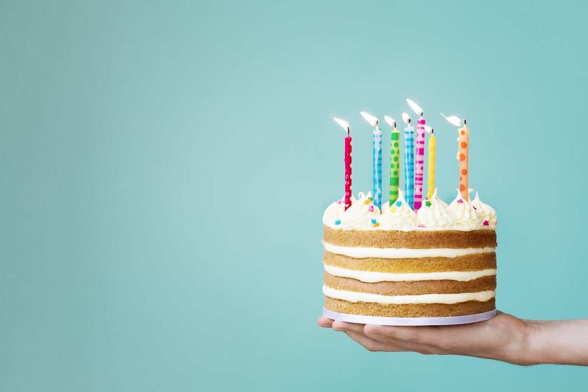 Hand holding a layered vanilla cake with colorful candles