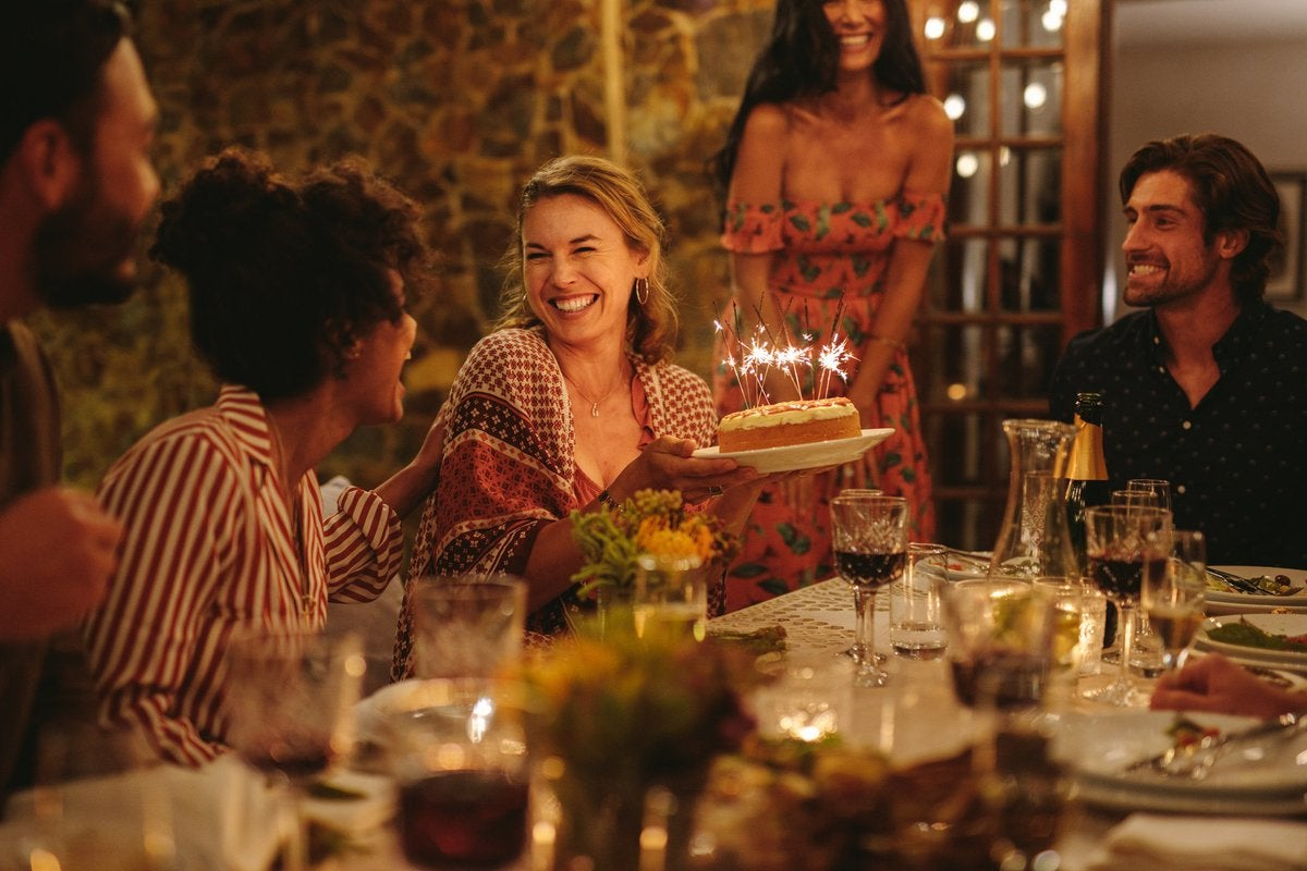 A woman holding a birthday cake at a dinner party with her friends.