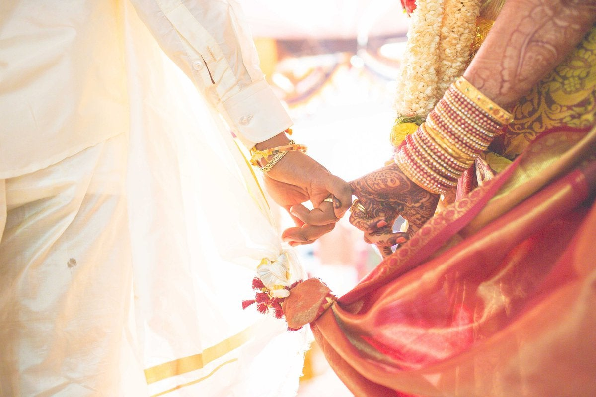 A bride with henna and bracelets on her arm holds hands with a groom.