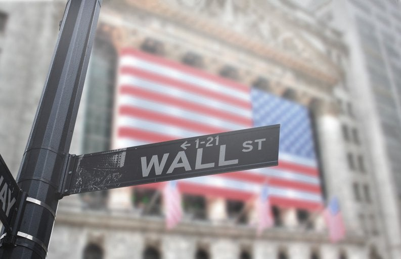 A street sign that says Wall St. with the American flag on a building in the background.