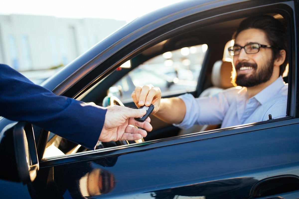 man sitting in car as salesman hands him the key through the window