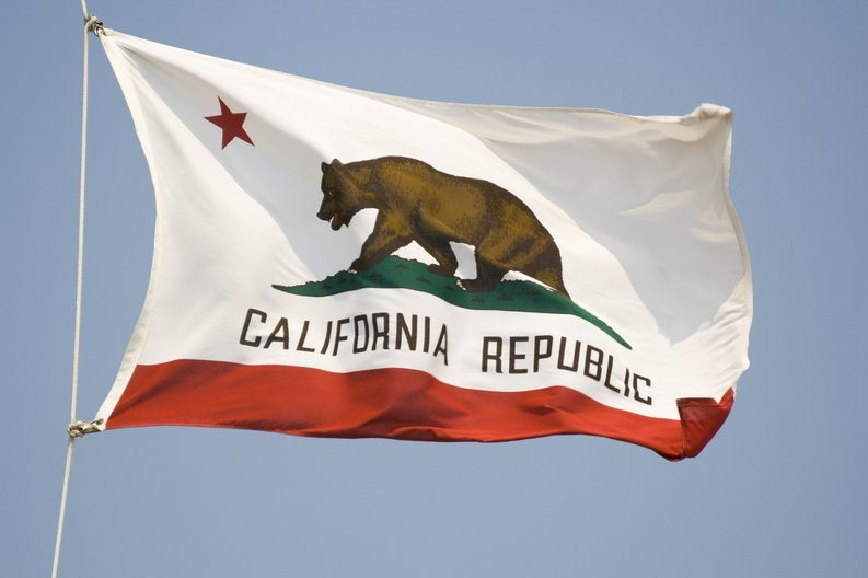 The California state flag fluttering in front of a blue sky.