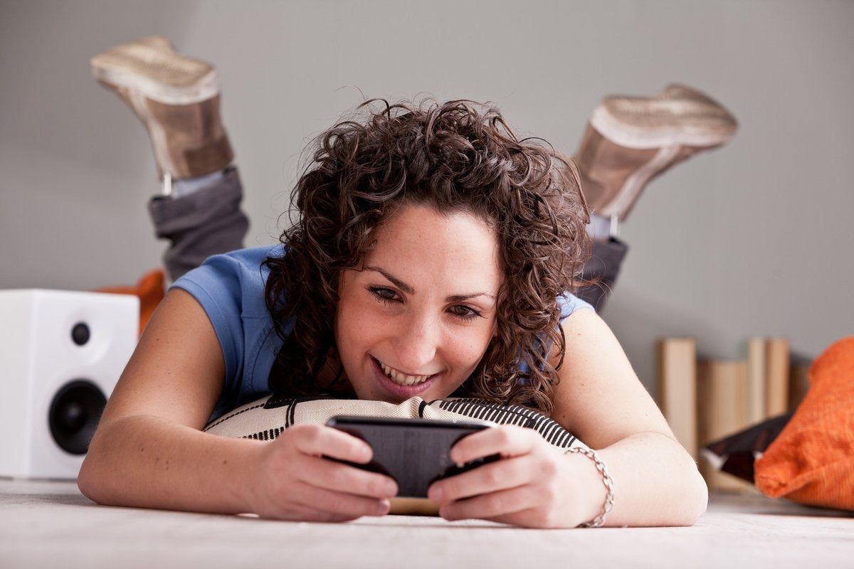 Woman laying on the floor using her cell phone.