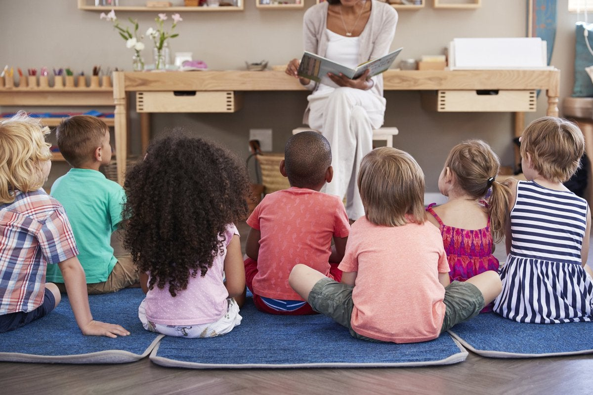Young children seated in front of a teacher reading a book