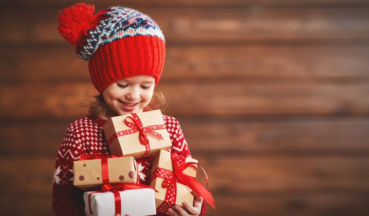 A grinning little girl in a knit cap holding an armful of gifts.