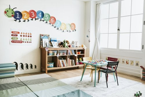 A kindergarten classroom with colorful books, chairs, and decorations.