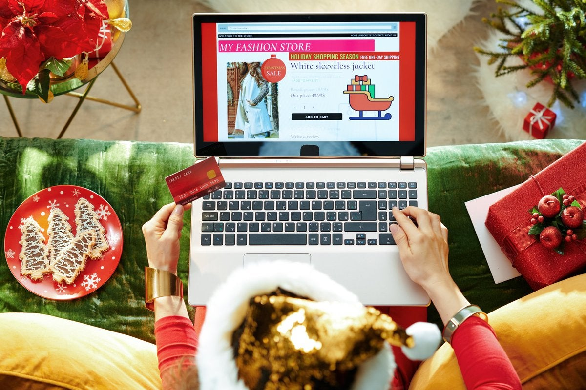 A woman online shopping surrounded by Christmas decorations.