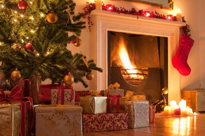 A Christmas tree and lots of presents in front of a fireplace.