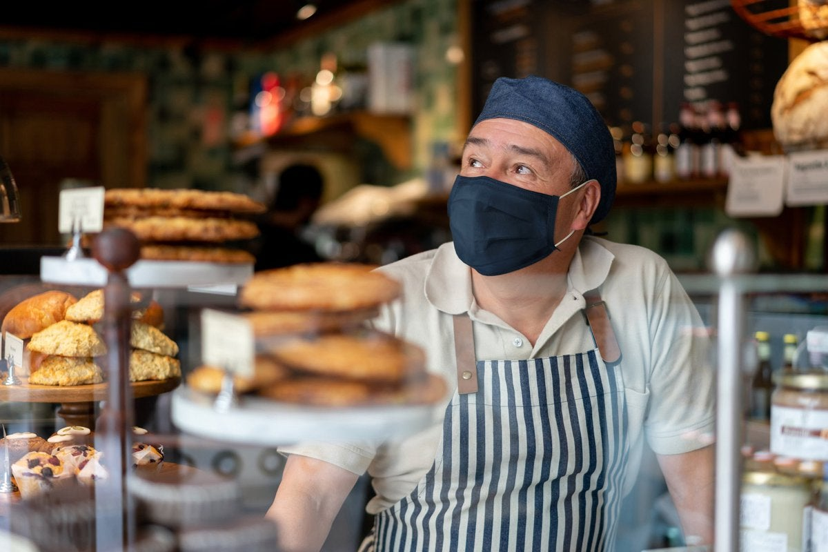 A coffee shop worker, wearing a face mask, looks off in the distance.