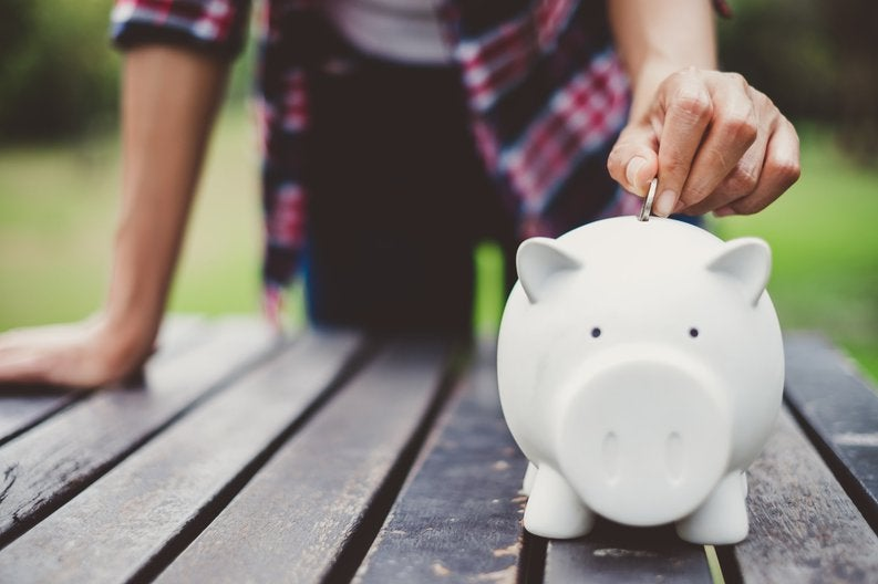 A person standing at a picnic table in a park and putting a coin in a piggy bank.
