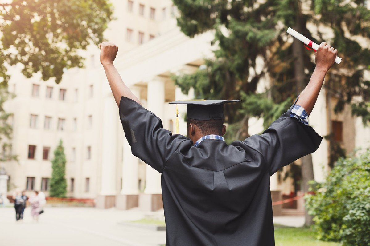 A person holding a diploma and wearing graduation robes celebrates.