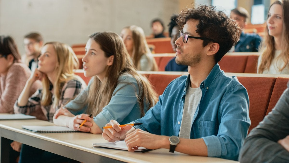 College students taking notes in a lecture hall.