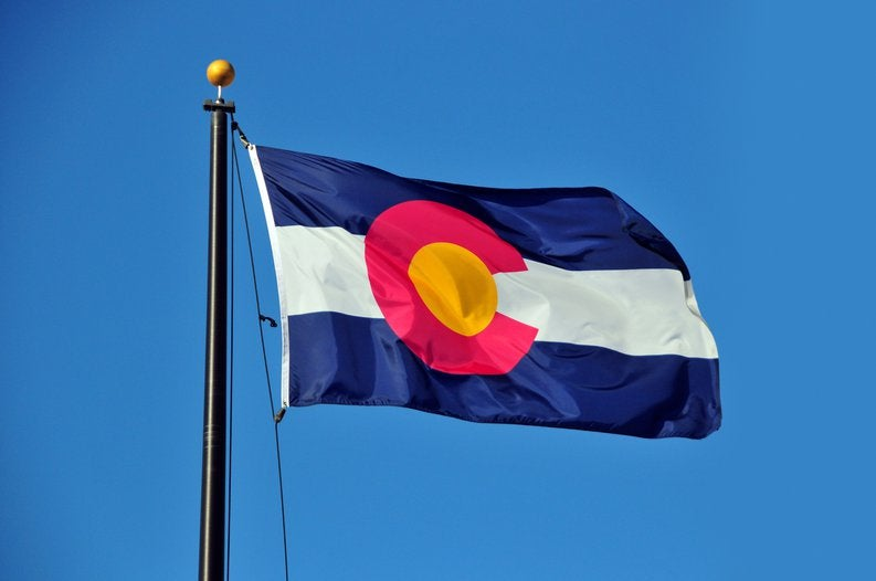 The Colorado state flag fluttering in front of a blue sky.