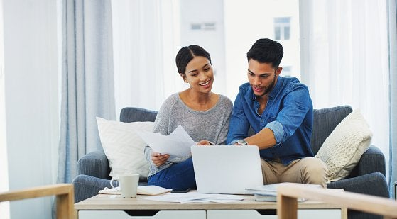 Couple Doing Paperwork With Laptop