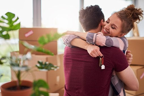 Couple Hugging With Keys To New House.jpg