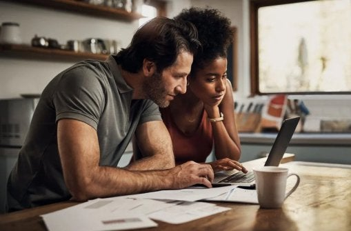 A man and woman sitting at their kitchen table with papers spread around them while researching something on a laptop.