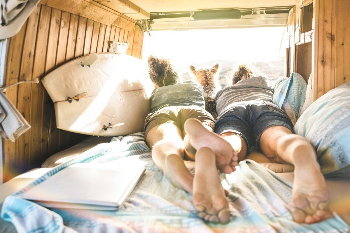 Young couple and their dog lying in a camper van next to a surfboard.