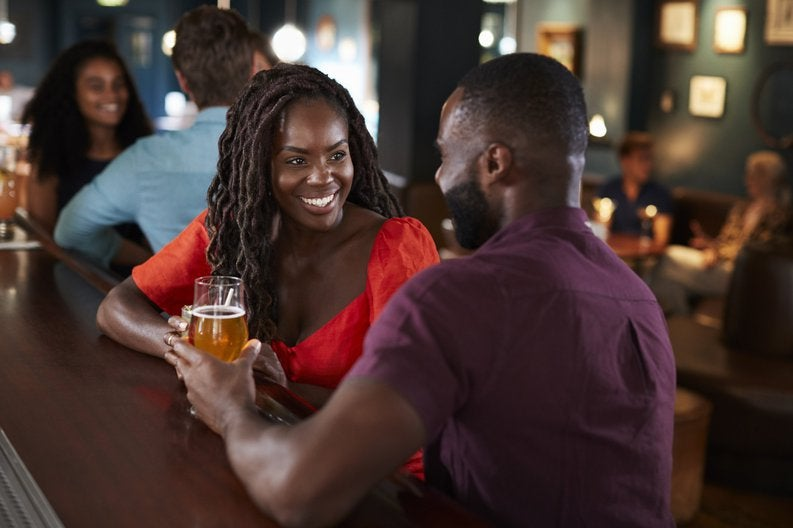 A smiling couple at a bar on a first date.