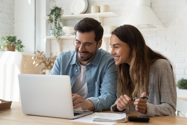 A happy man and woman look at a laptop screen.