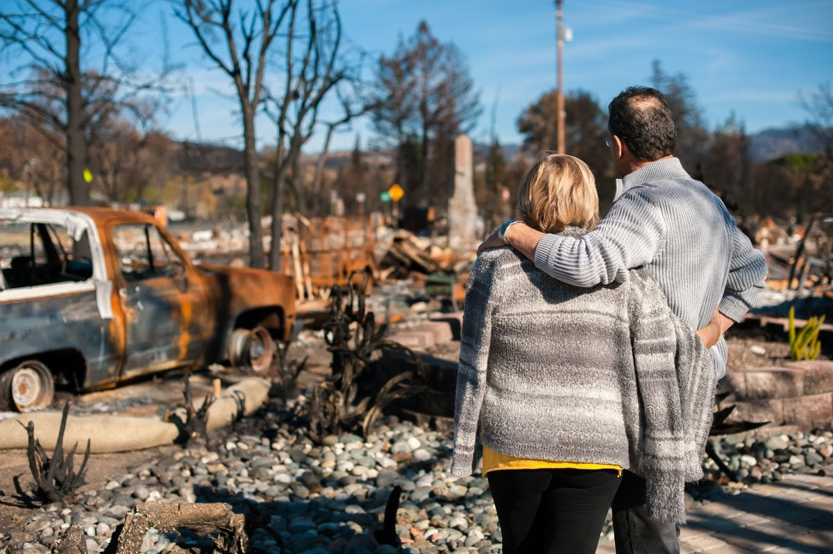 Couple checking ruins after fire disaster.