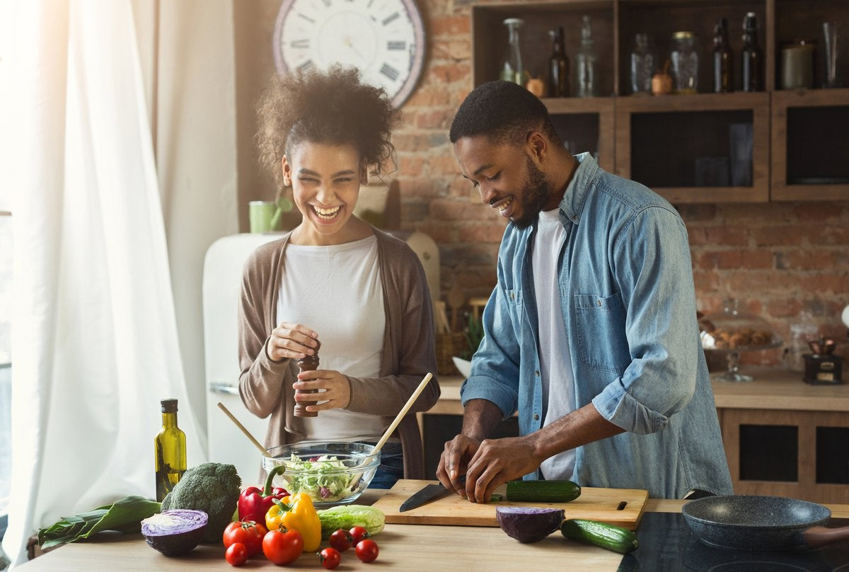 Young smiling couple cooking together at home.