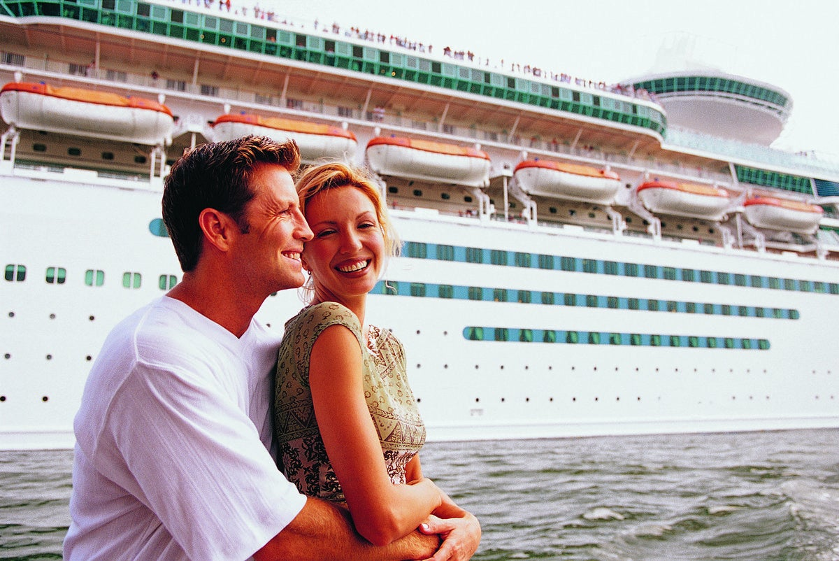 Couple embracing in front of cruise ship.