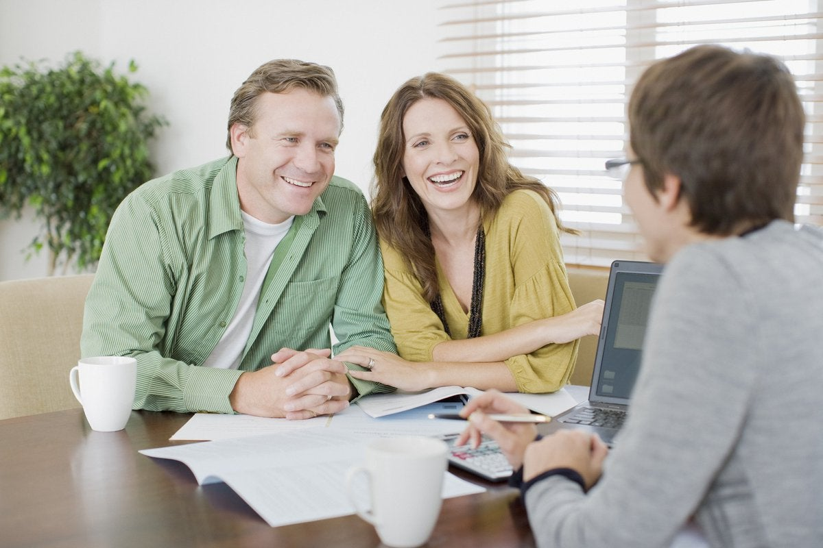 A smiling couple meeting with an advisor.